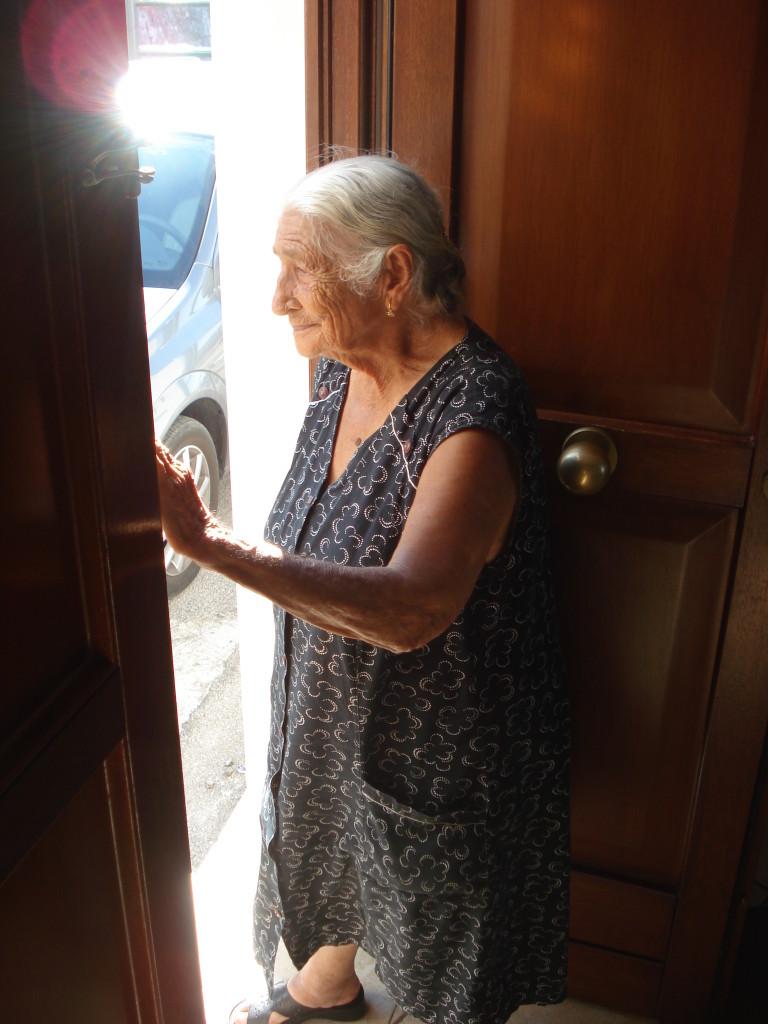 Anziana donna assiste da casa la vestizione